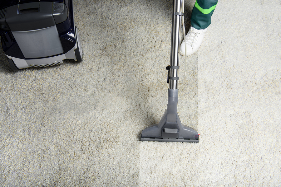 someone is cleaning the white dirty carpet using a vacuum