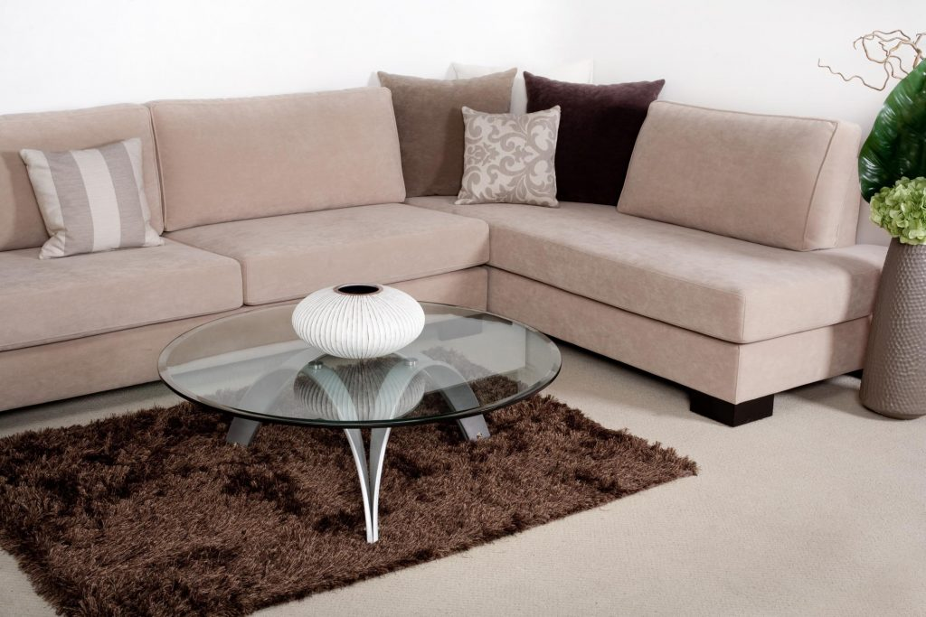 clean sofa with pillows and glass side table