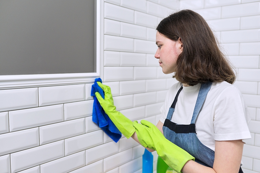 girl cleaning the gap tiles using a rug
