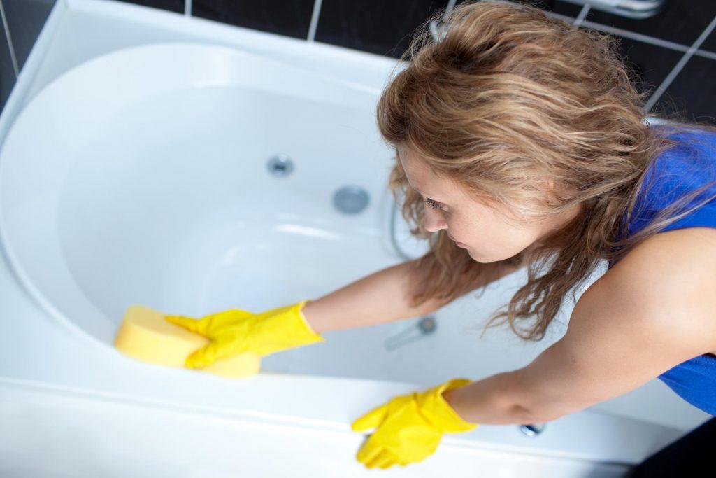 girl cleaning the bathtub using a sponge