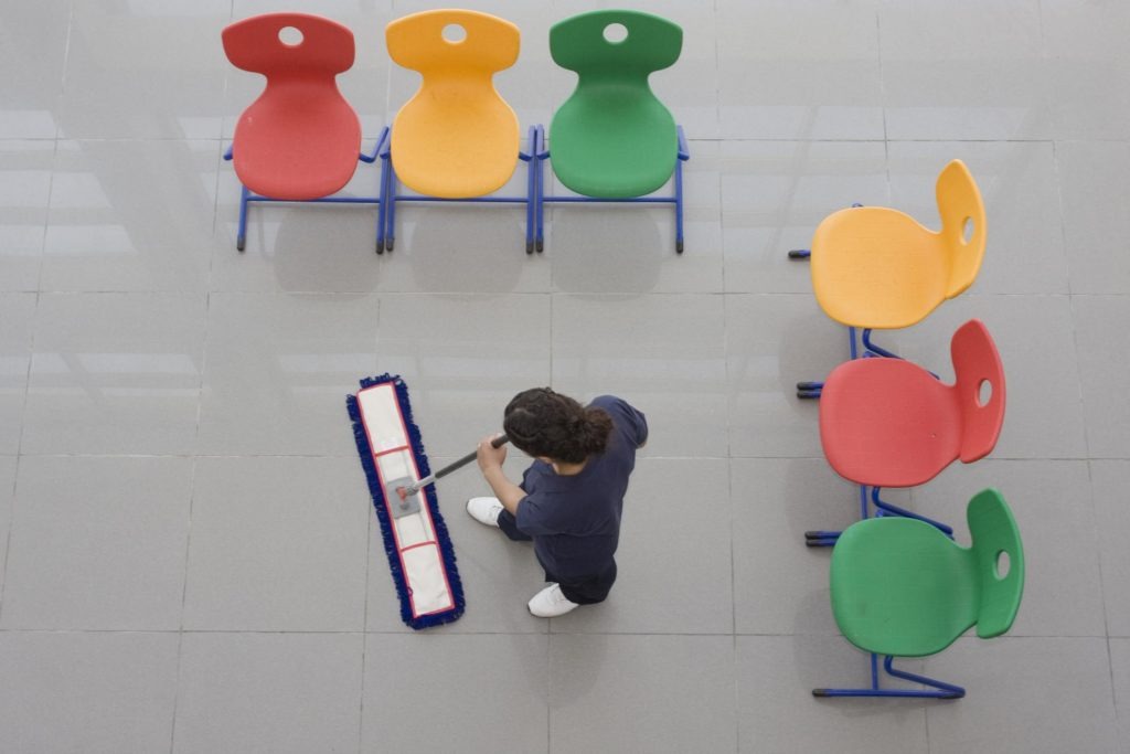 girl in braids is cleaning the floor surrounded with chairs