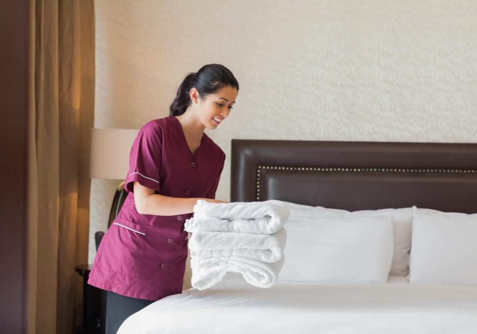 maintenance girl folding the white towels